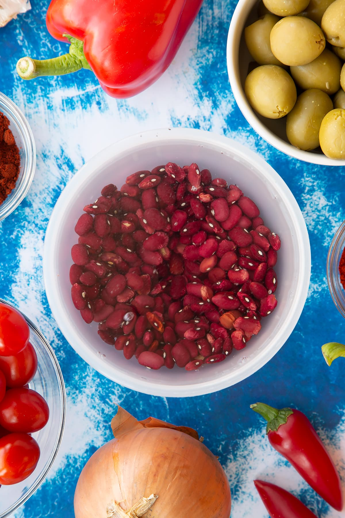 Dried kidney beans covered with water in a small pot. Ingredients to make easy Spanish rice and beans surround the pot.