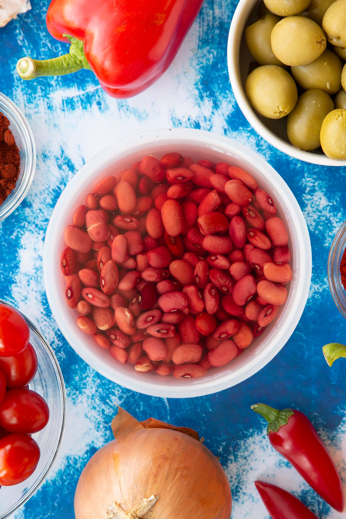 Soaked kidney beans in a small pot. Ingredients to make easy Spanish rice and beans surround the pot.