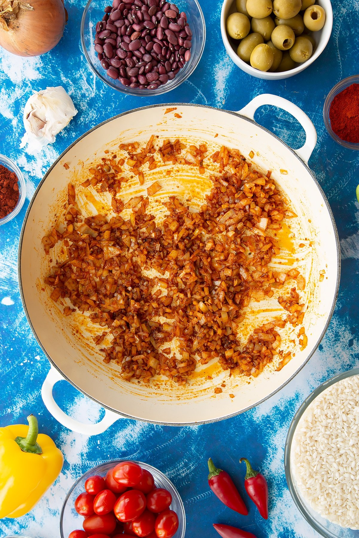 Sweated onions, garlic, cayenne, paprika and oregano in a pan. Ingredients to make easy Spanish rice and beans surround the pan.