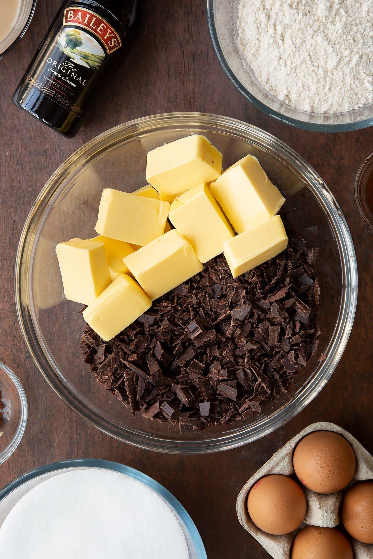 Chopped dark chocolate and cubed butter in a glass bowl. Ingredients to make Baileys brownies surround the bowl.