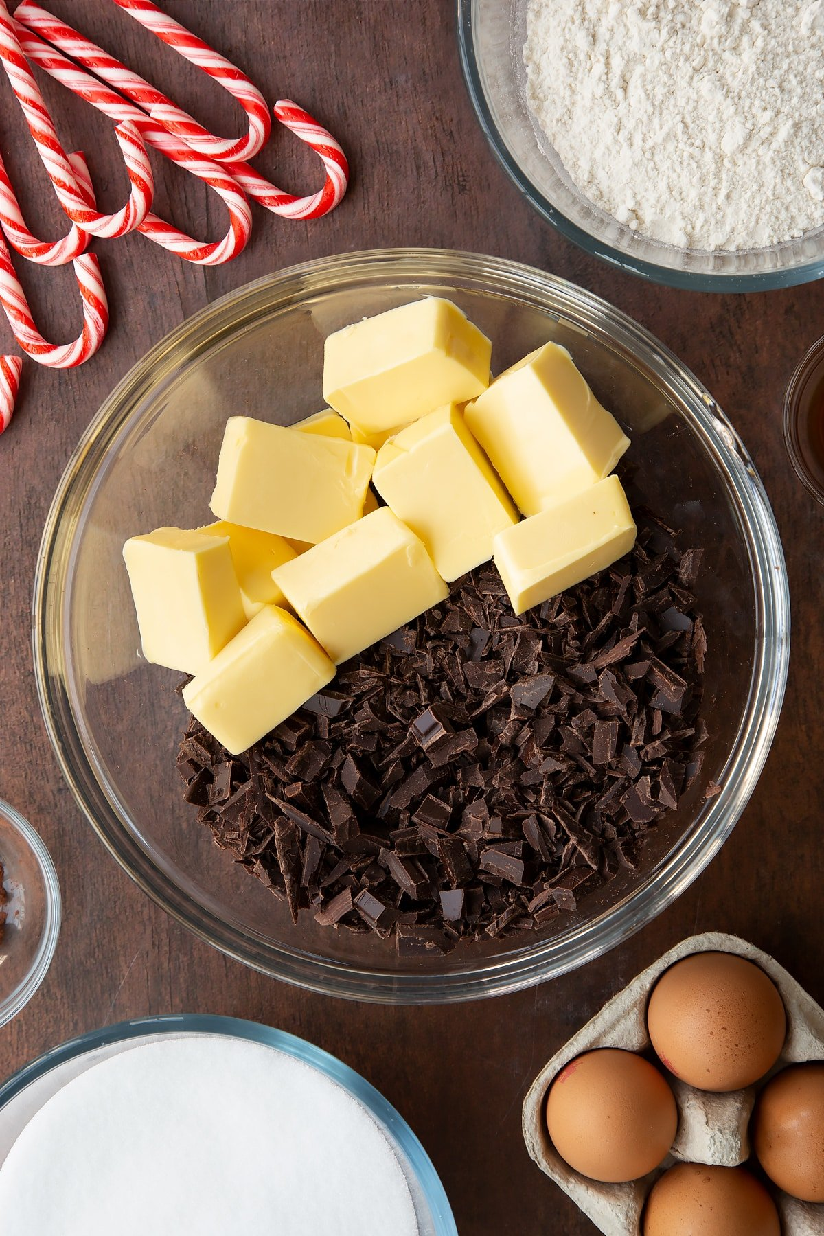 Cubed butter and chopped dark chocolate in a glass bowl. Ingredients to make Candy cane brownies surround the bowl.