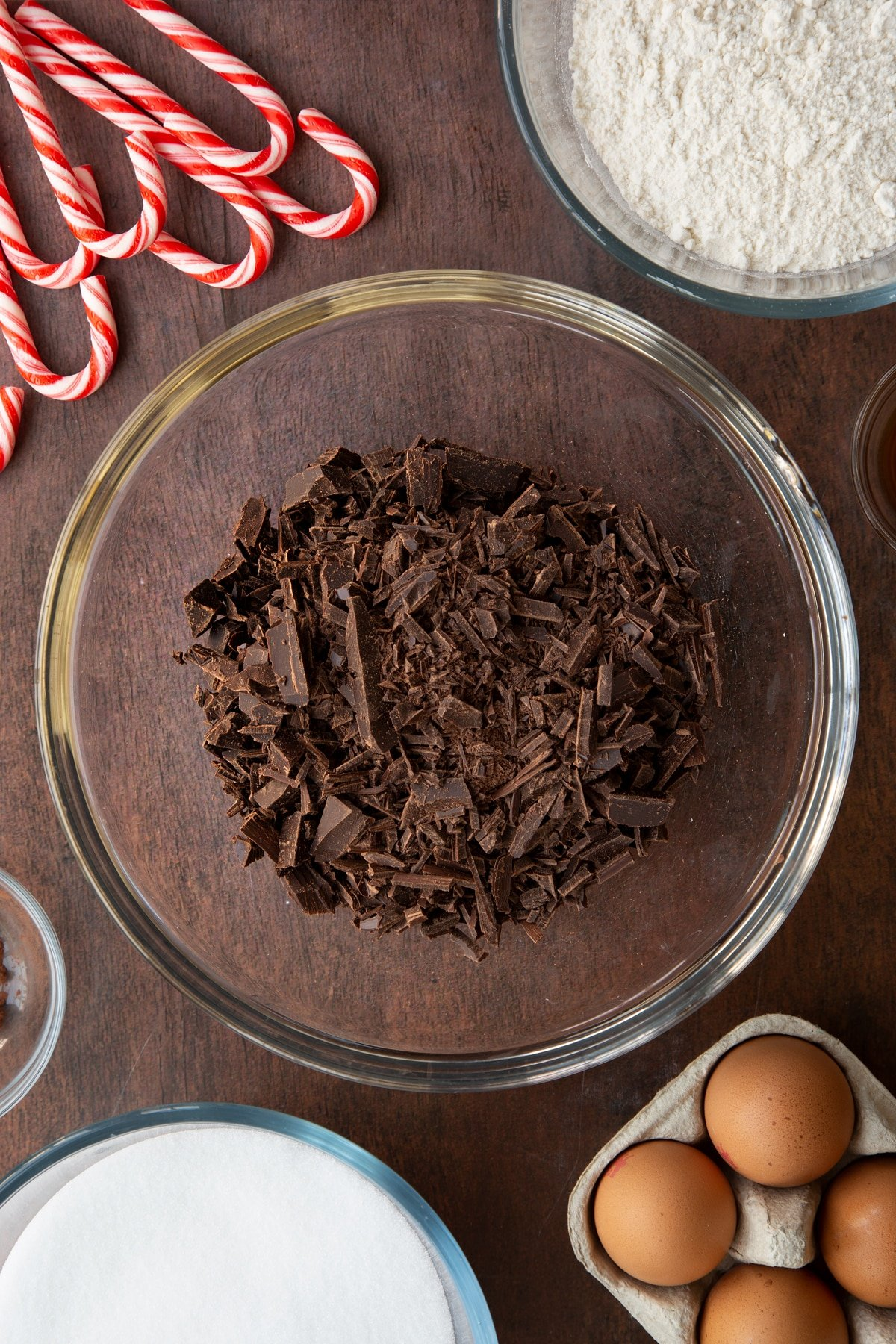 Chopped dark chocolate in a glass bowl. Ingredients to make Candy cane brownies surround the bowl.