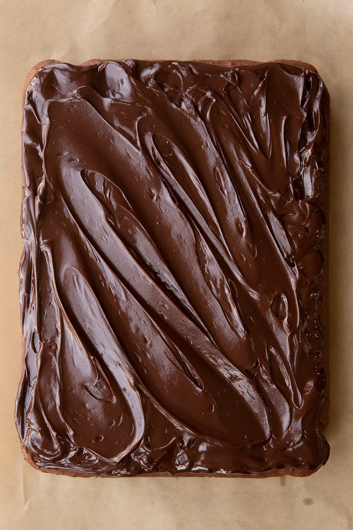Baked candy cane brownie on baking paper with dark chocolate ganache spread on top.