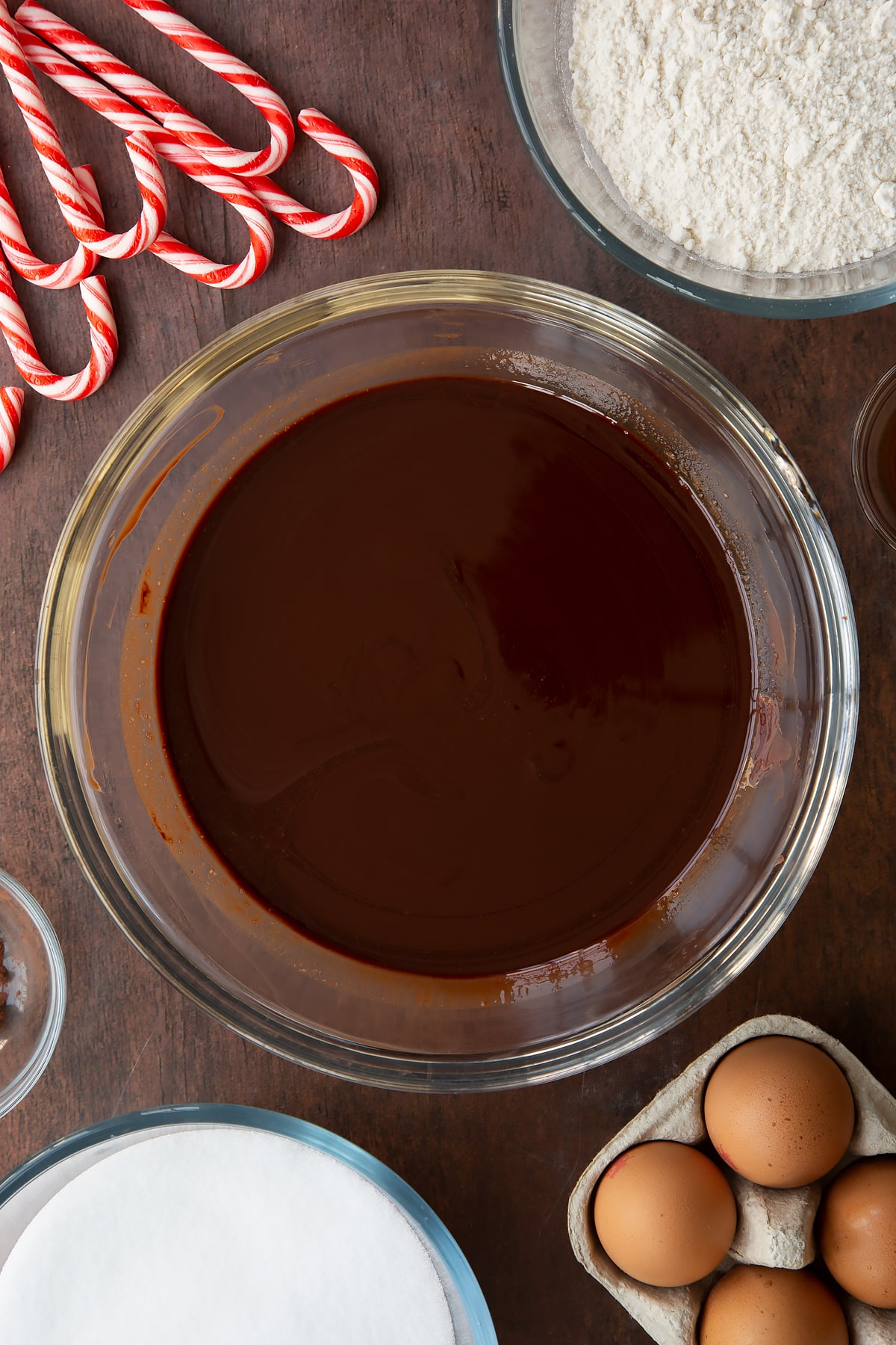 Melted butter and dark chocolate in a glass bowl. Ingredients to make Candy cane brownies surround the bowl.