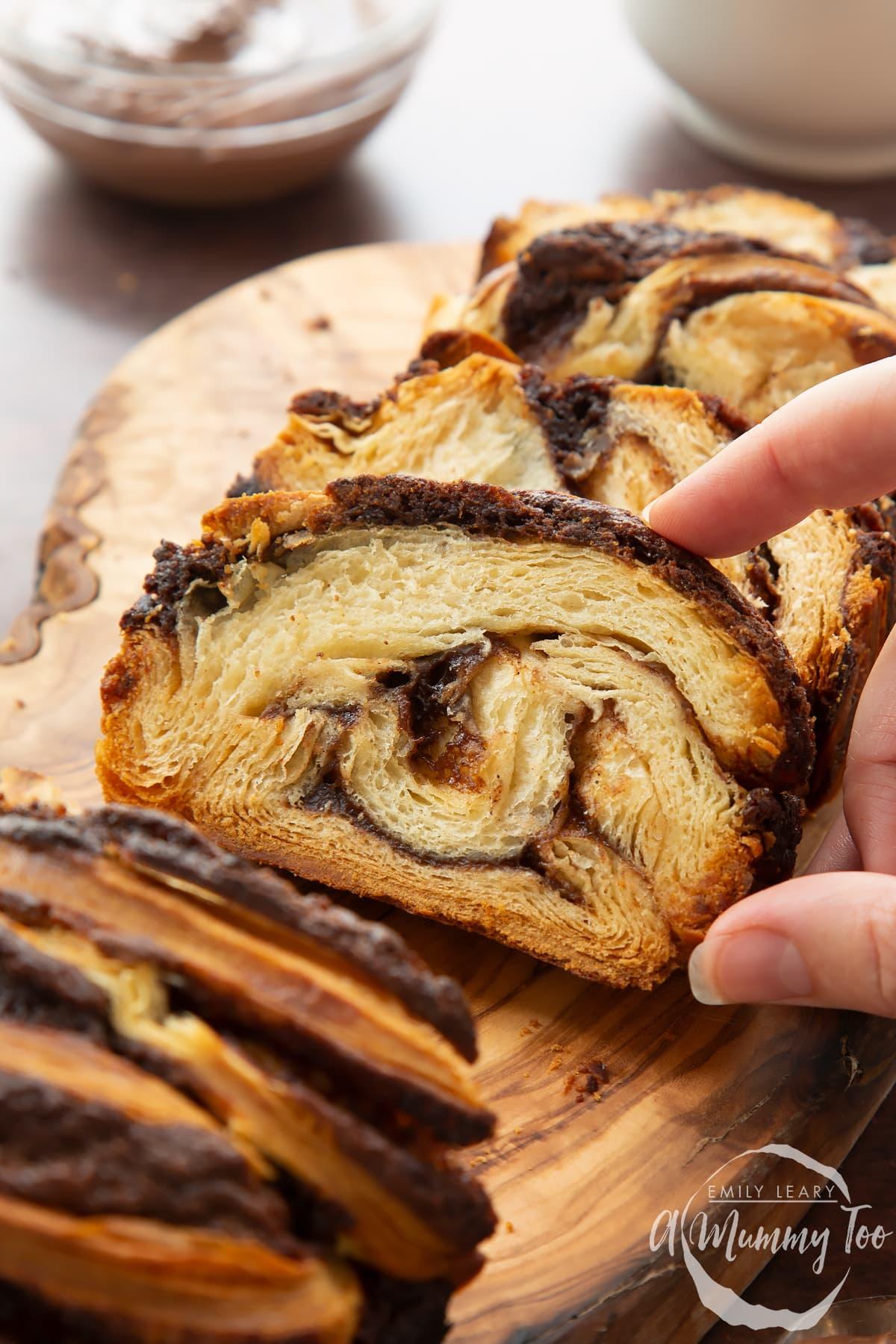 Hand reaching for a slice of cinnamon swirl babka on a wooden board.