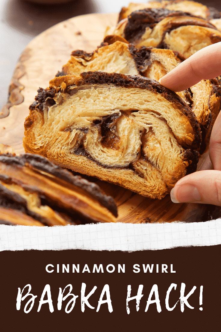 Hand reaching for a slice of cinnamon swirl babka on a wooden board. Caption reads: cinnamon swirl babka hack!