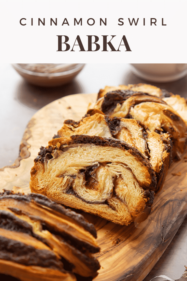Slices of cinnamon swirl babka on a wooden board. Caption reads: cinnamon swirl babka