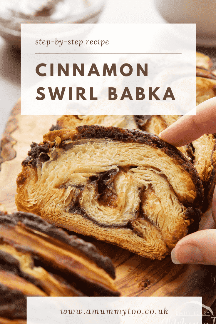 Hand reaching for a slice of cinnamon swirl babka on a wooden board. Caption reads: step-by-step recipe cinnamon swirl babka