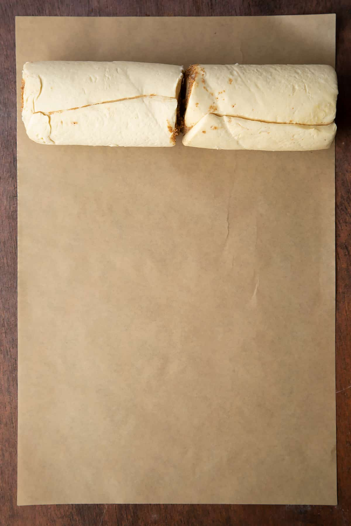 Two rolls of cinnamon swirl dough on a piece of brown baking paper.