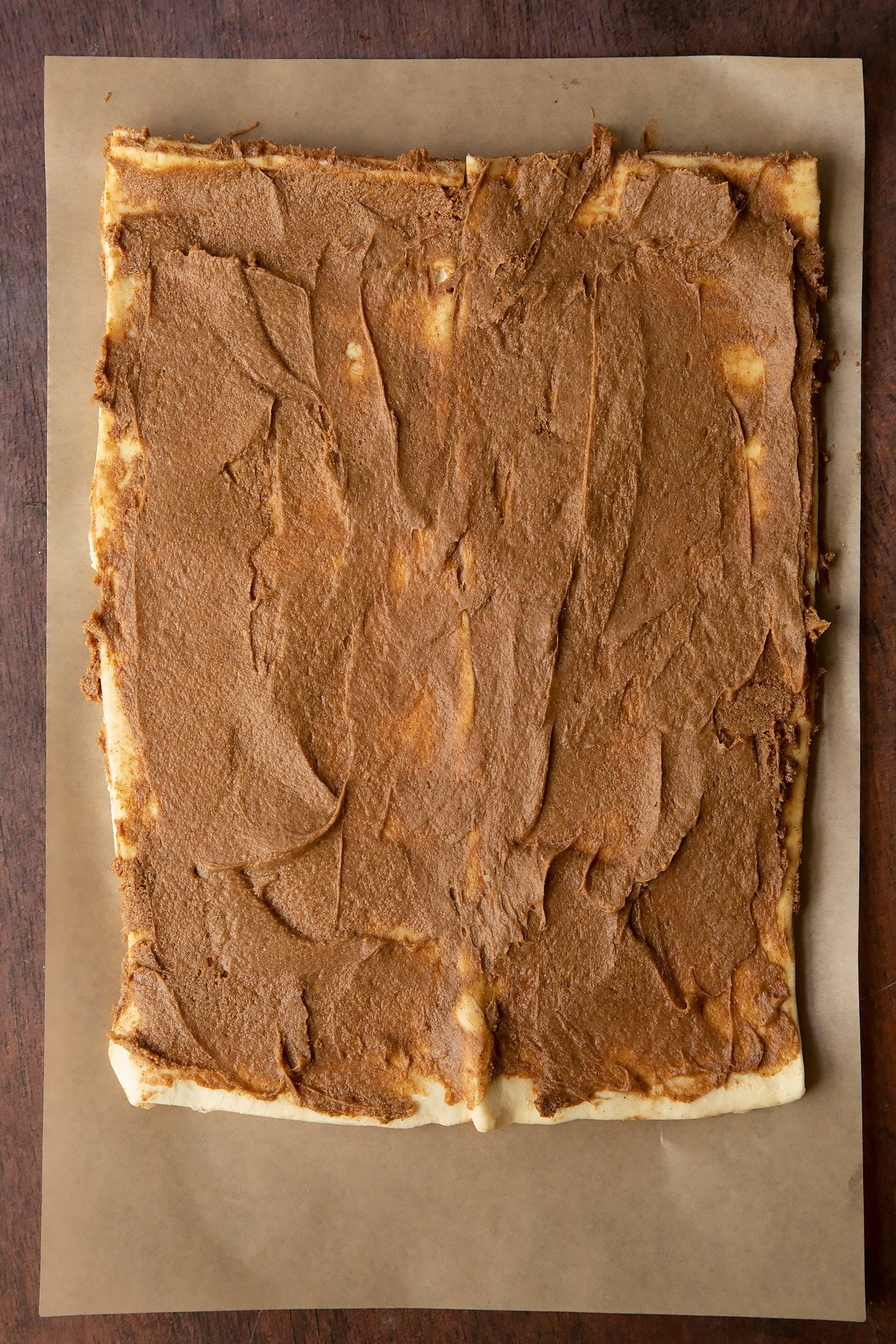 Two strips of unrolled cinnamon swirl dough on a piece of brown baking paper. The cinnamon butter filling is spread evenly.