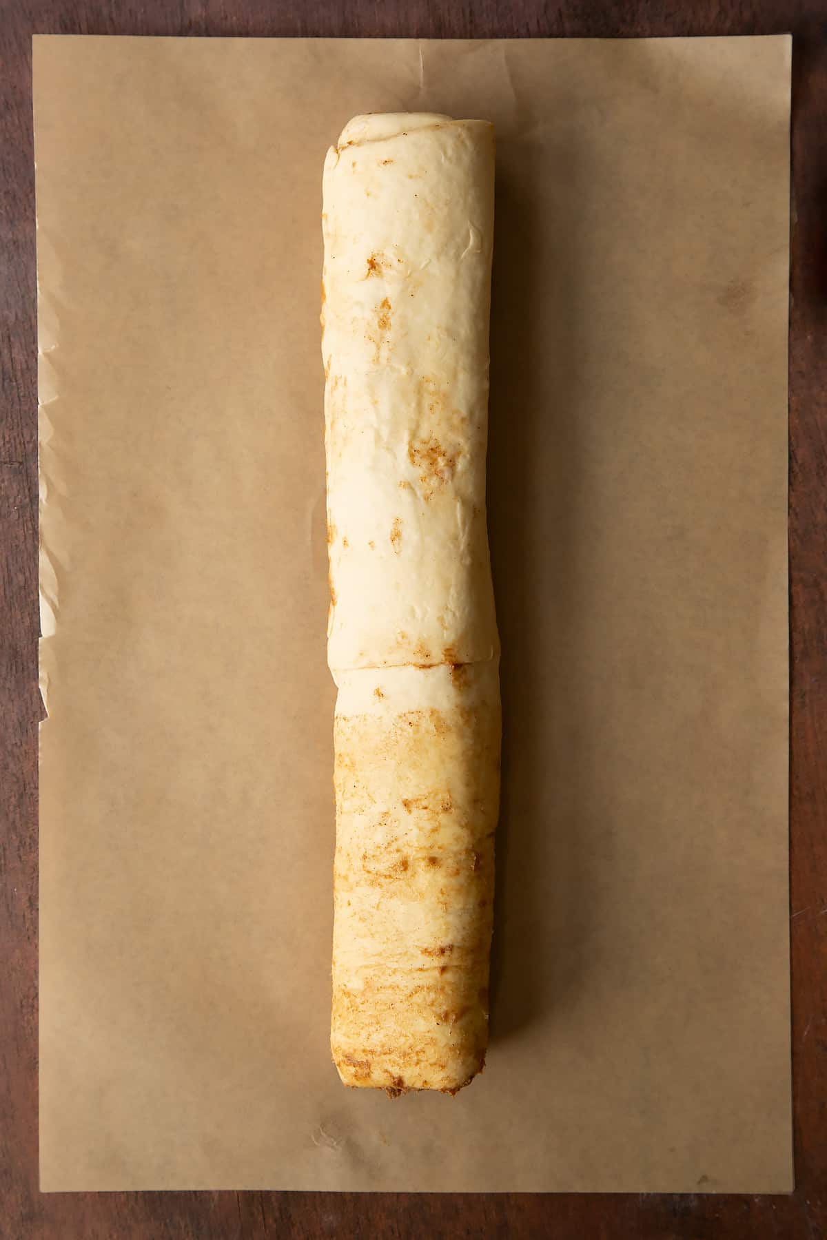 Cinnamon swirl dough rolled along the length to create a long sausage.
