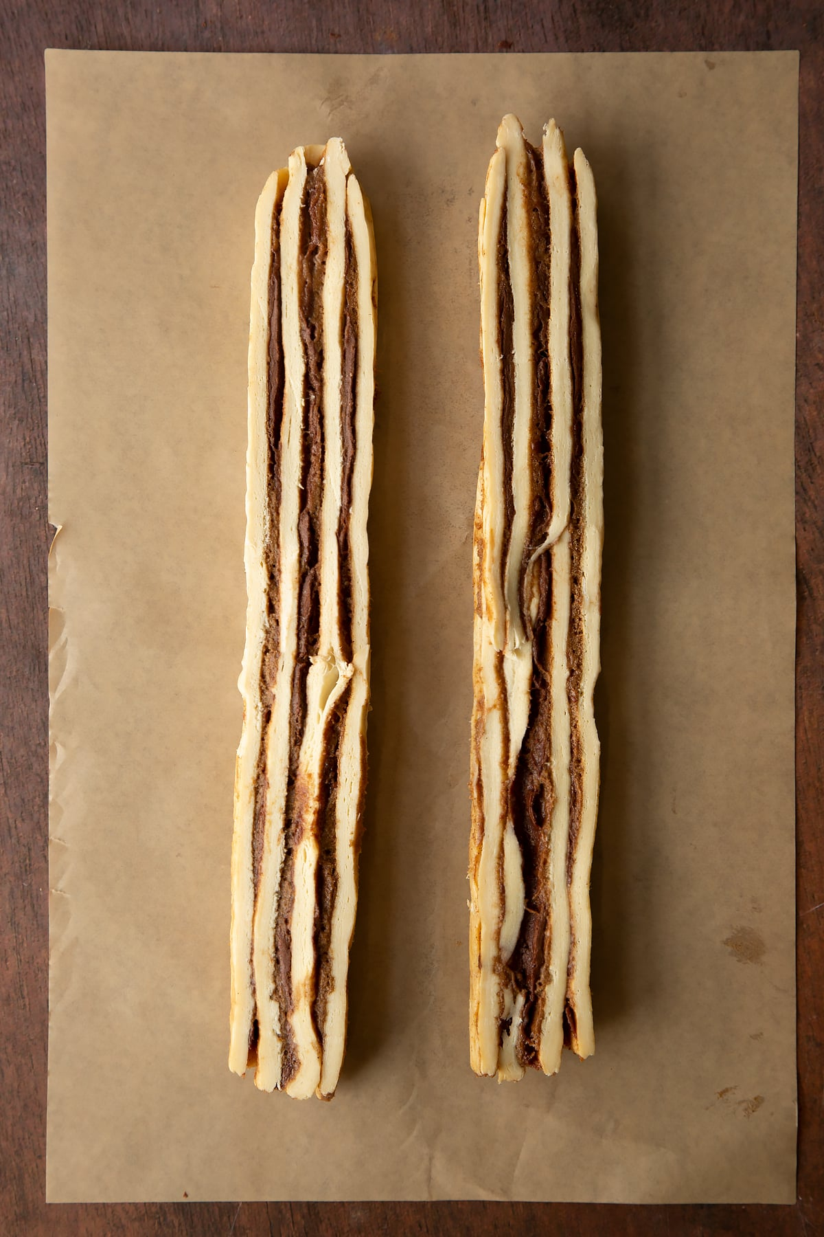 Cinnamon swirl dough rolled along the length to create a long sausage, then sliced down the length to create two striped pieces.