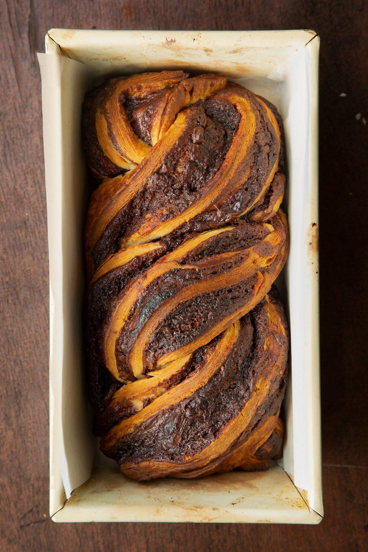 Baked cinnamon swirl babka in a lined baking tin.