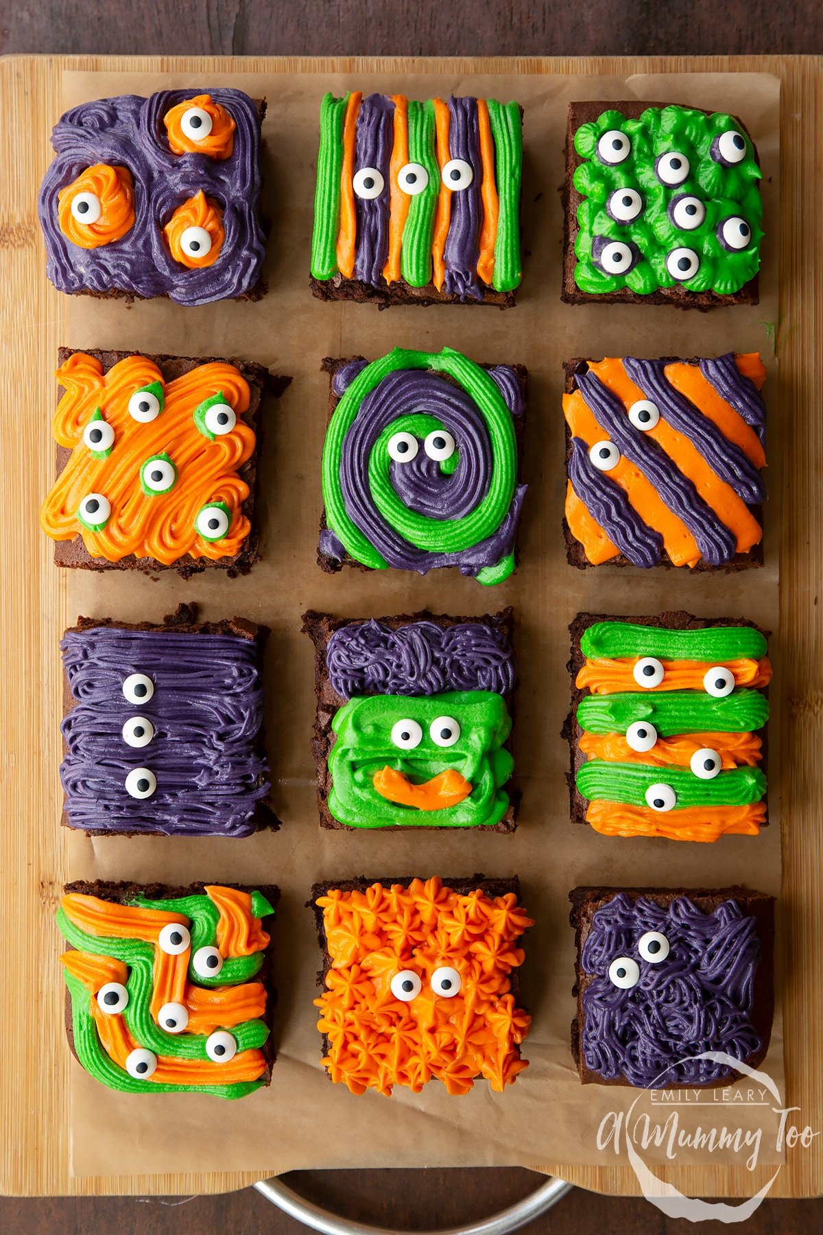 12 Halloween brownies arranged on a board lined with baking paper. The brownies are decorated with purple, green and orange frosting and candy eyes.