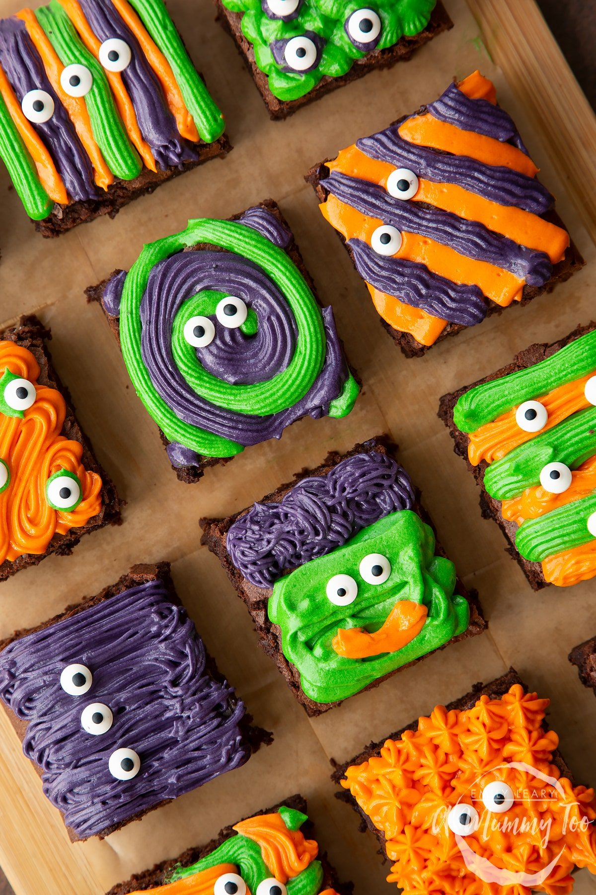 Halloween brownies arranged on a board lined with baking paper. The brownies are decorated with purple, green and orange frosting and candy eyes.