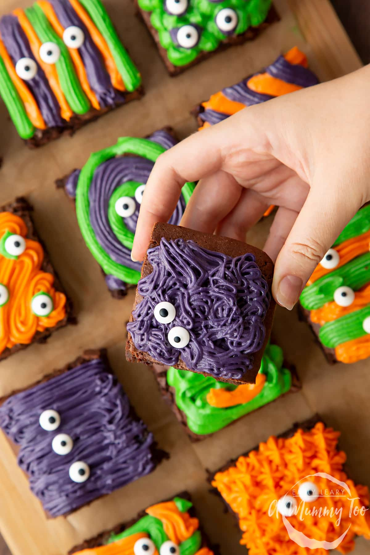 Halloween brownies arranged on a board lined with baking paper. A hand holds a purple frosted brownie with candy eyes.