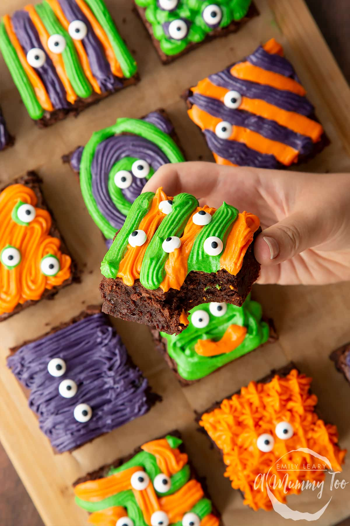 Halloween brownies arranged on a board lined with baking paper. A hand holds a purple and green frosted brownie with candy eyes.