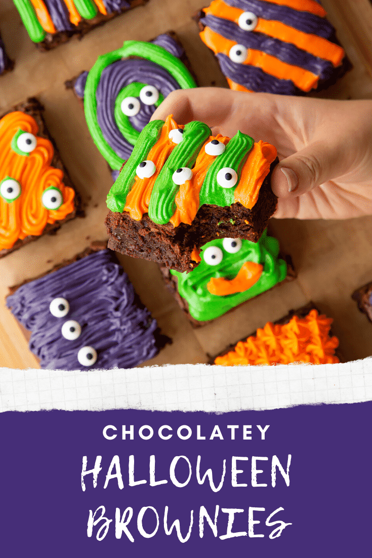 Halloween brownies arranged on a board lined with baking paper. A hand holds a orange and green frosted one. Caption reads: chocolatey Halloween brownies