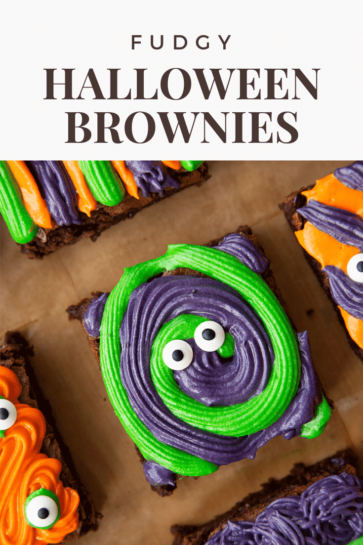 Close up of a purple and green frosted Halloween brownie with candy eyes, resting on a board lined with baking paper. Caption reads: fudgy Halloween brownies