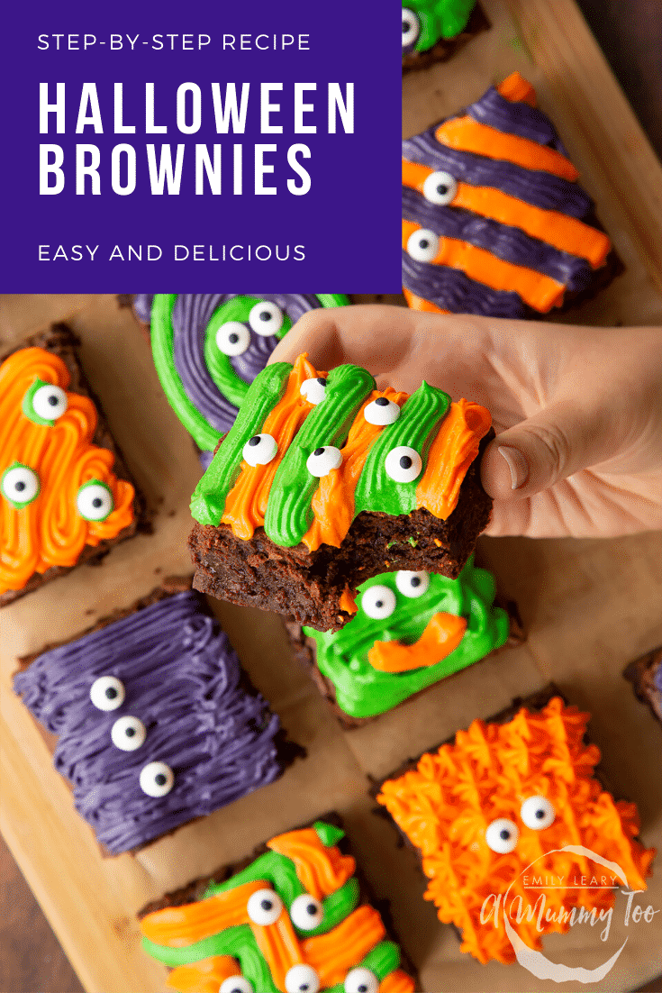 Halloween brownies arranged on a board lined with baking paper. A hand holds a purple and green frosted brownie with candy eyes. Caption reads: step-by-step recipe Halloween brownies easy and delicious