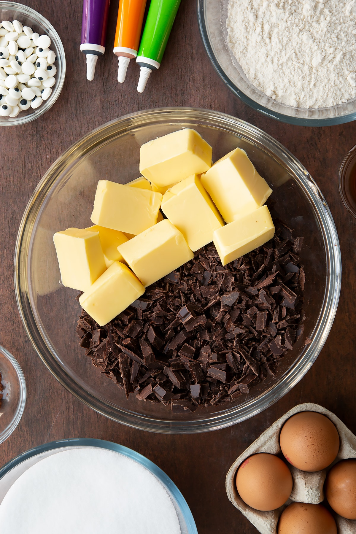 Butter and chopped dark chocolate in a glass bowl. Ingredients to make Halloween brownies surround the bowl.