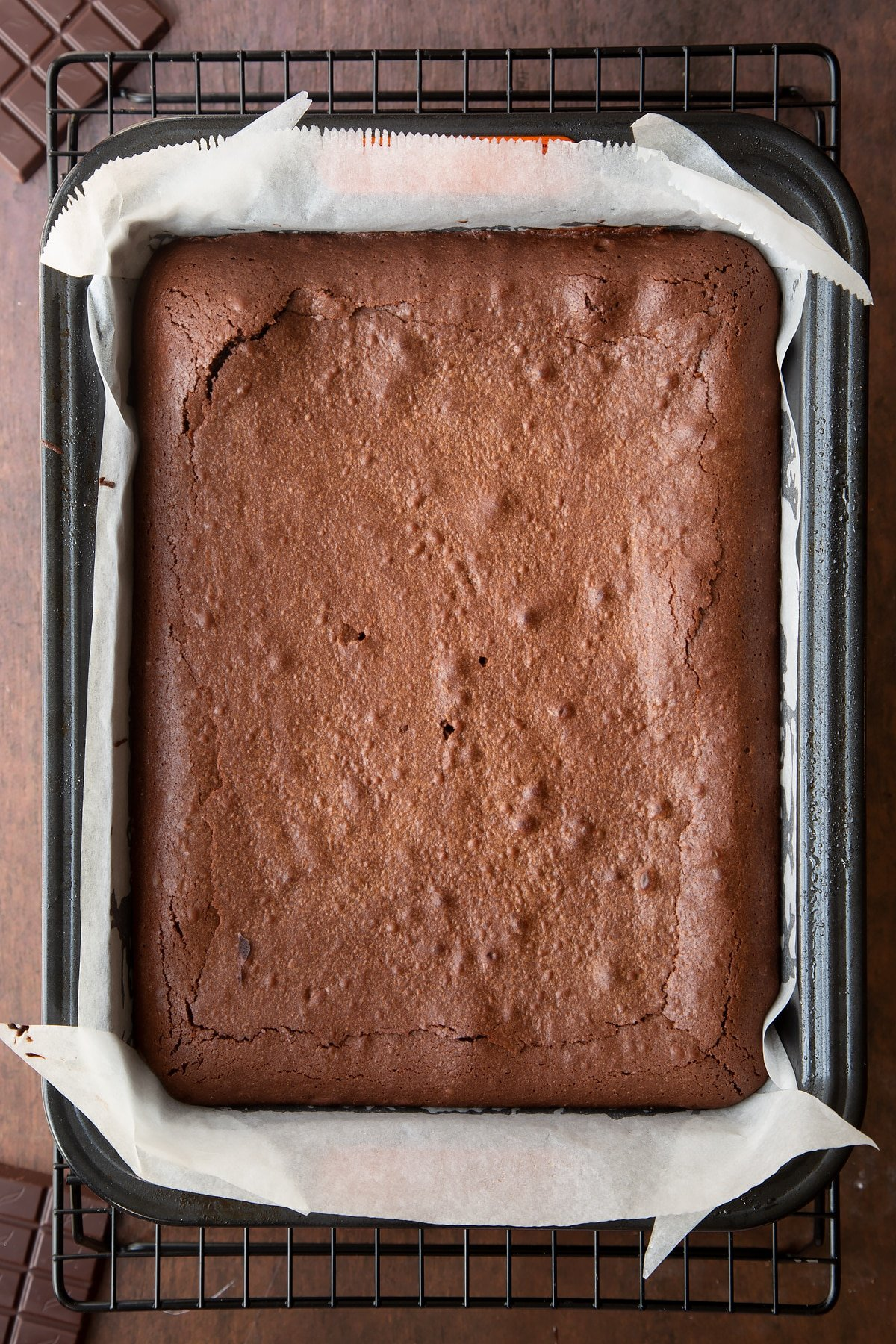 Freshly baked Halloween brownie in a lined tin.