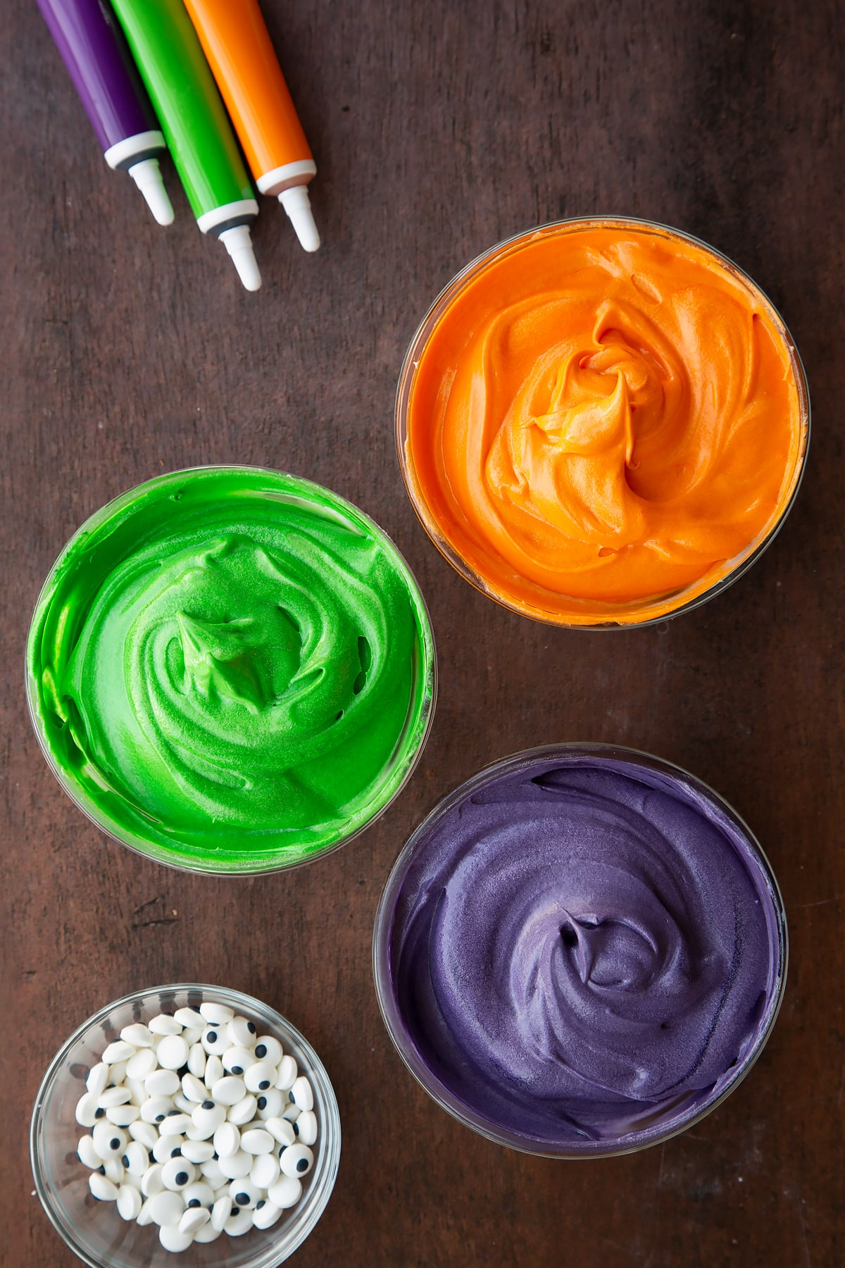 Cream cheese frosting in three glass bowls, coloured orange, green or purple.