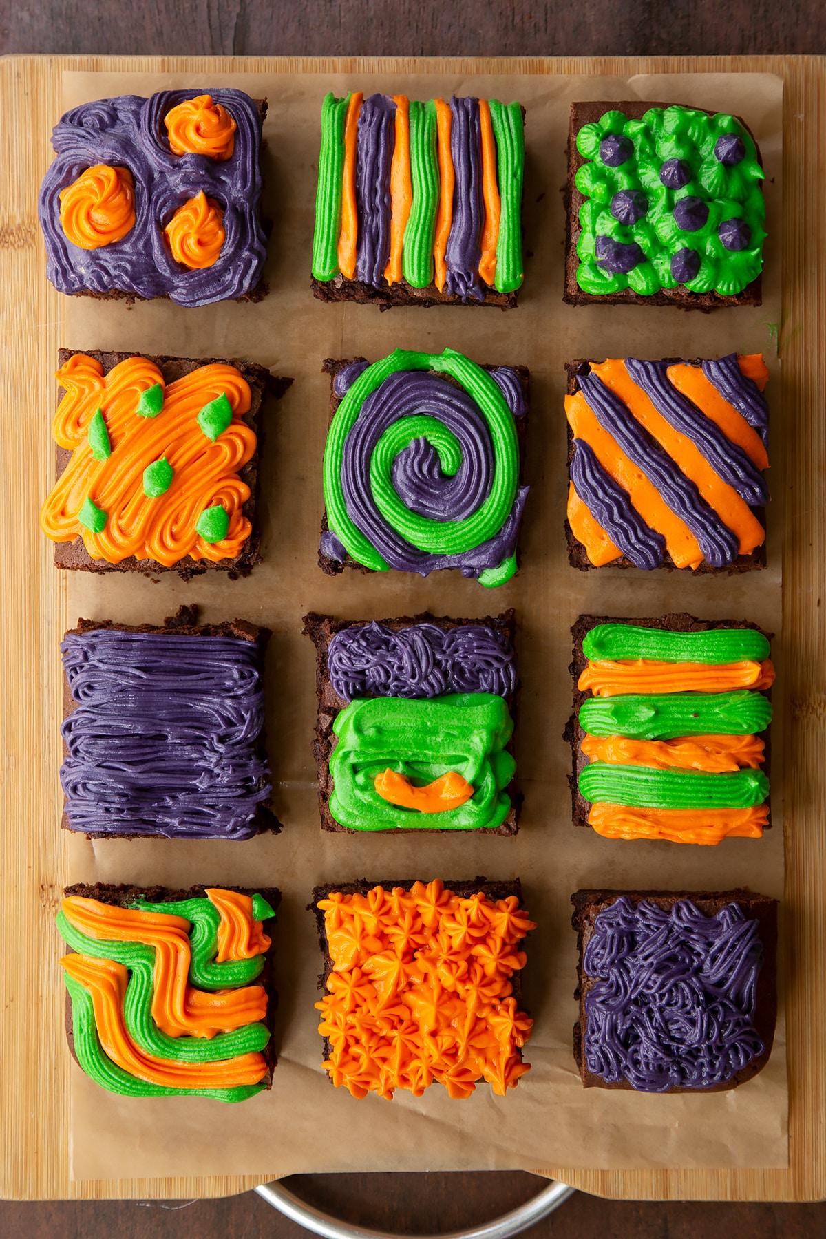 Halloween brownie on baking paper, cut into 12 pieces. Orange, green and purple frosting has been piped on top of the brownies in various patterns.