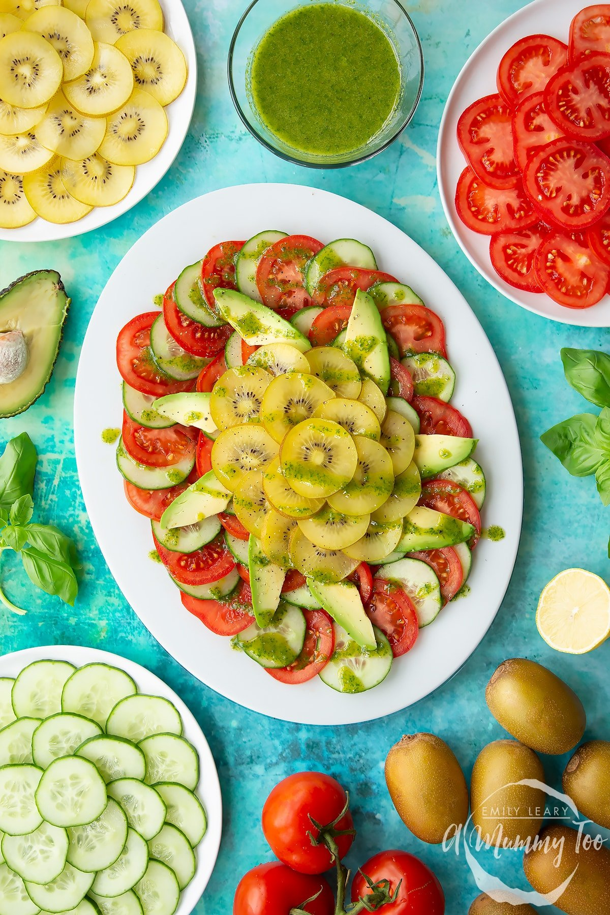 Kiwi salad with basil oil on an oval white platter, surrounded by ingredients.