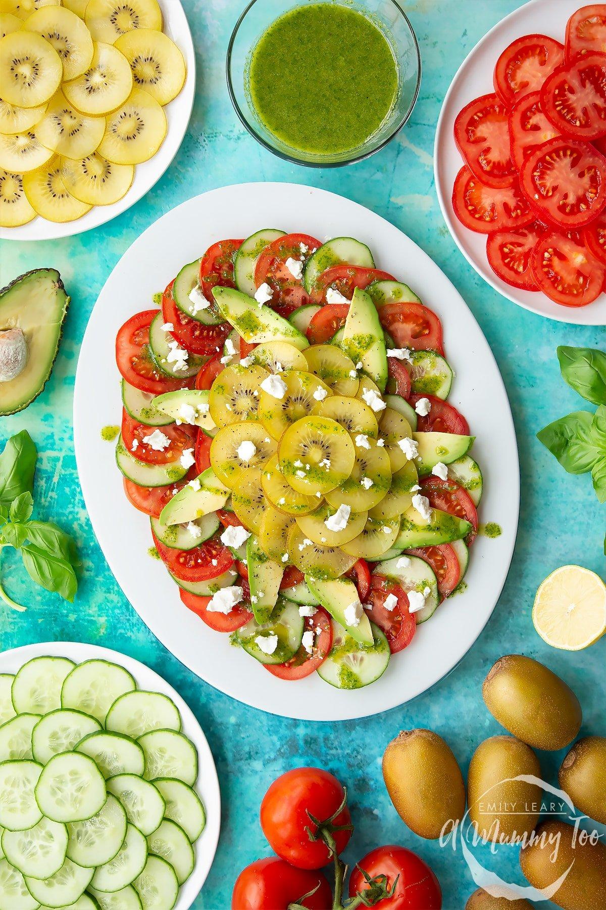 Kiwi feta salad with basil oil on an oval white platter.