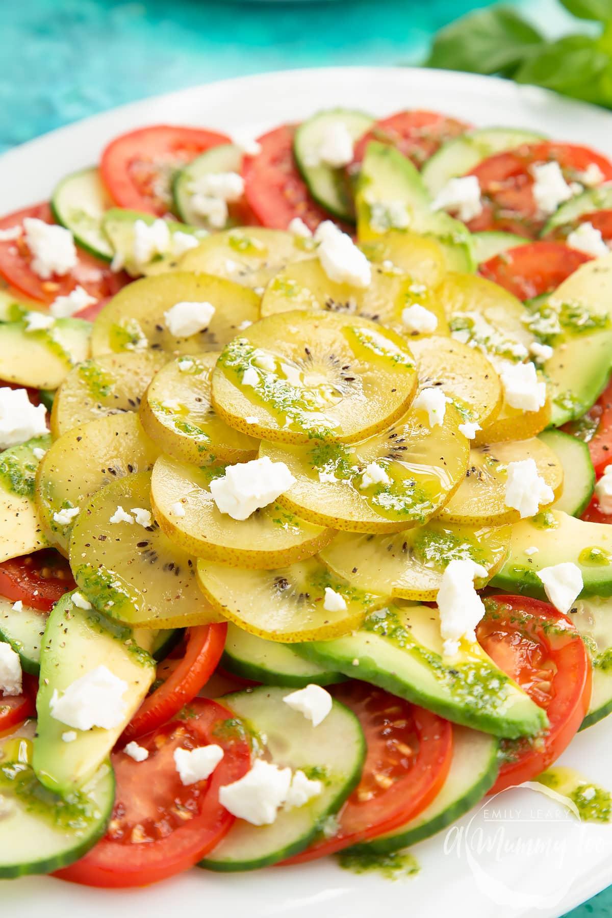 Close up of kiwi feta salad with basil oil on a white platter.