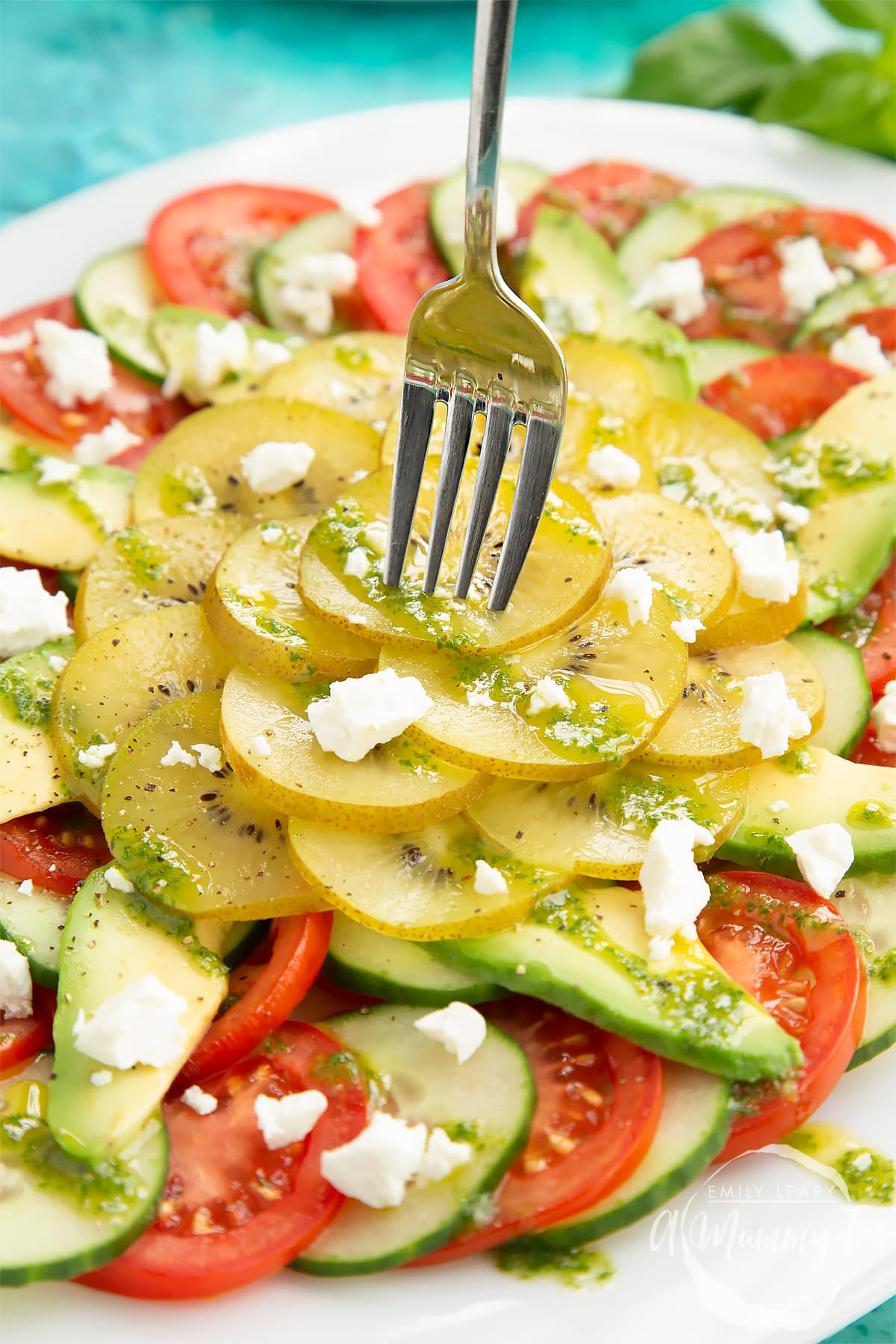 Close up of kiwi feta salad with basil oil on a white platter. A fork digs into the salad.