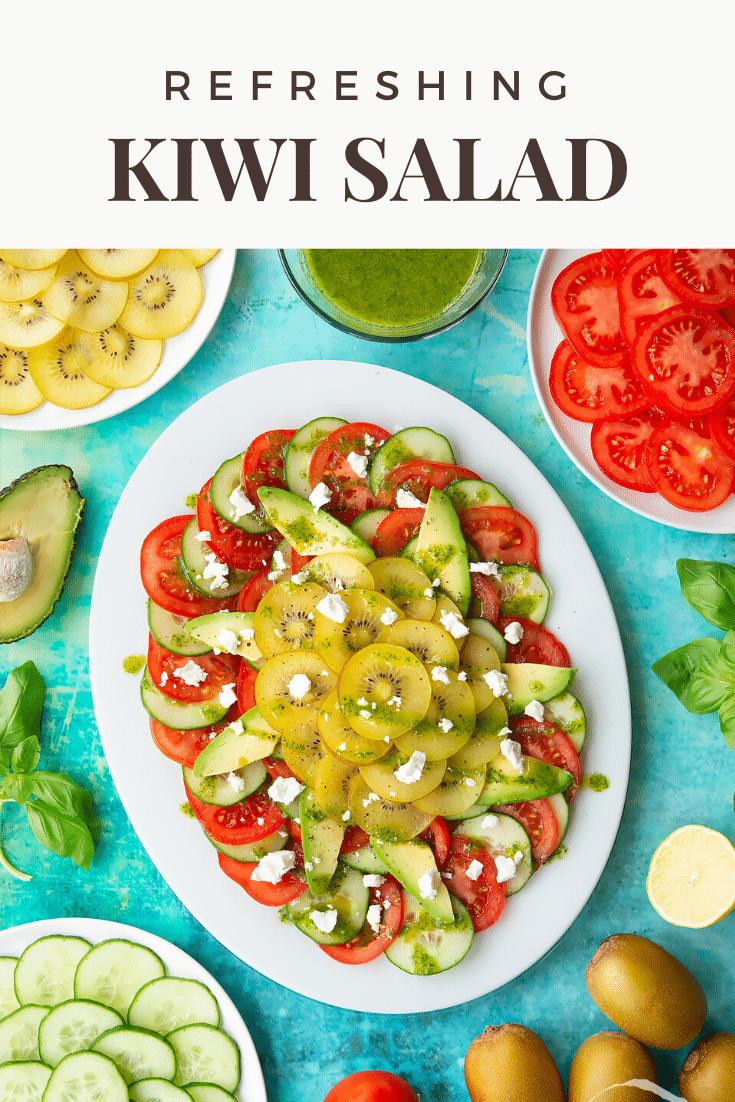 Kiwi feta salad on an oval white platter. Caption reads: Refreshing kiwi feta salad.