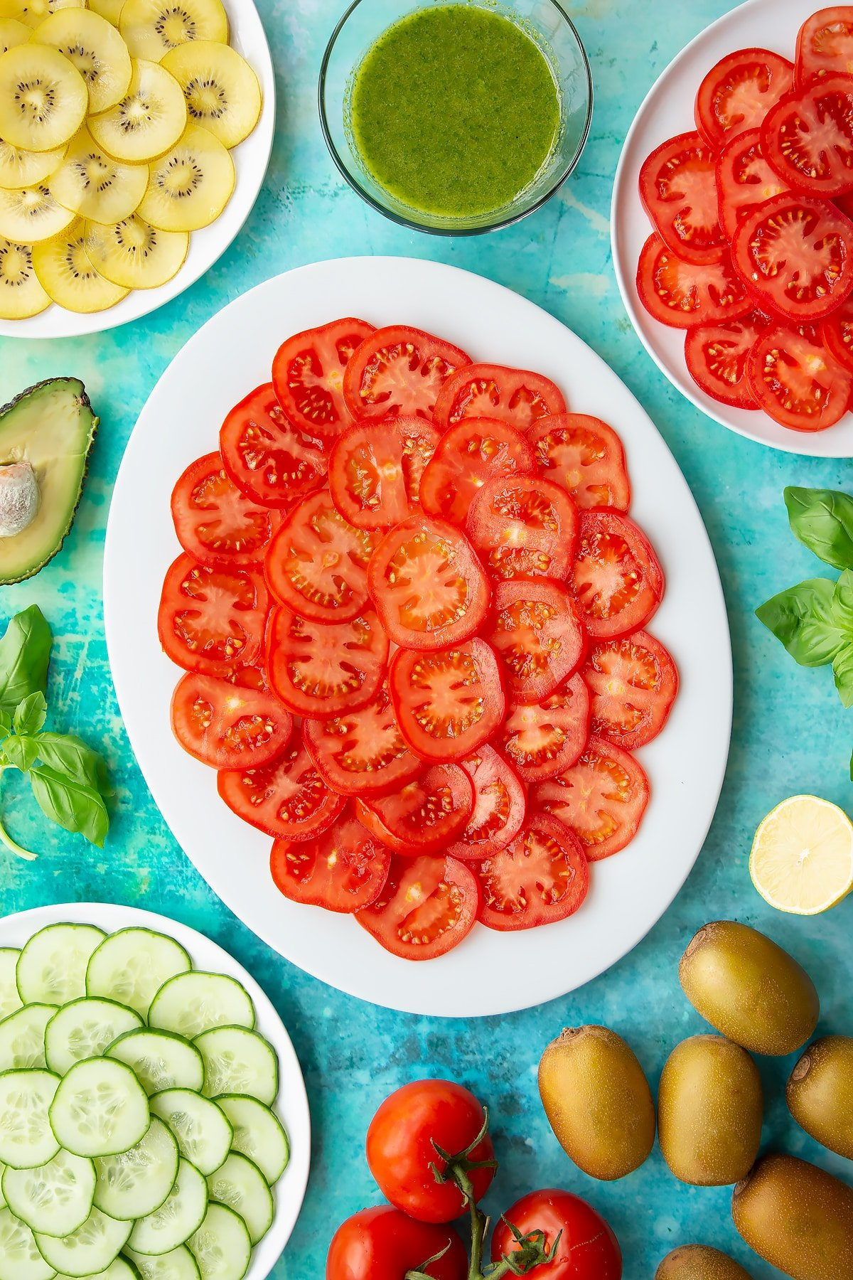 Sliced tomatoes on a white oval plate. Ingredients to make a kiwi feta salad surround the platter.