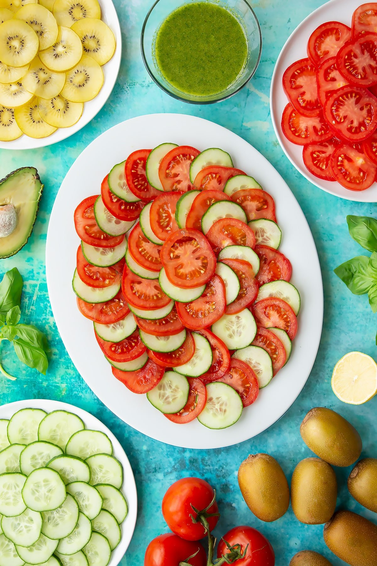 Sliced tomatoes and cucumber on a white oval plate. Ingredients to make a kiwi feta salad surround the platter.