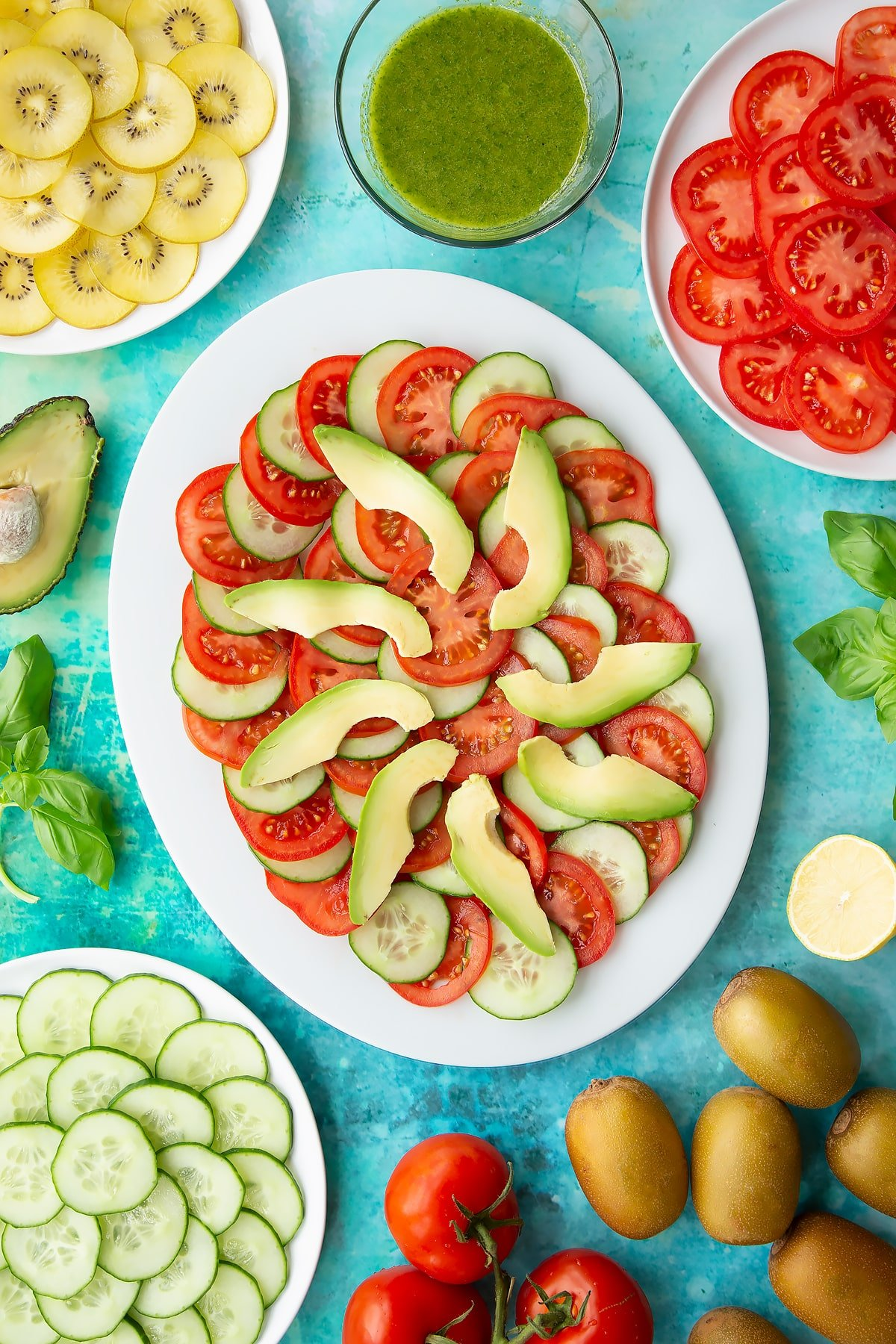 Sliced tomatoes, cucumber and avocado on a white oval plate. Ingredients to make a kiwi feta salad surround the platter.