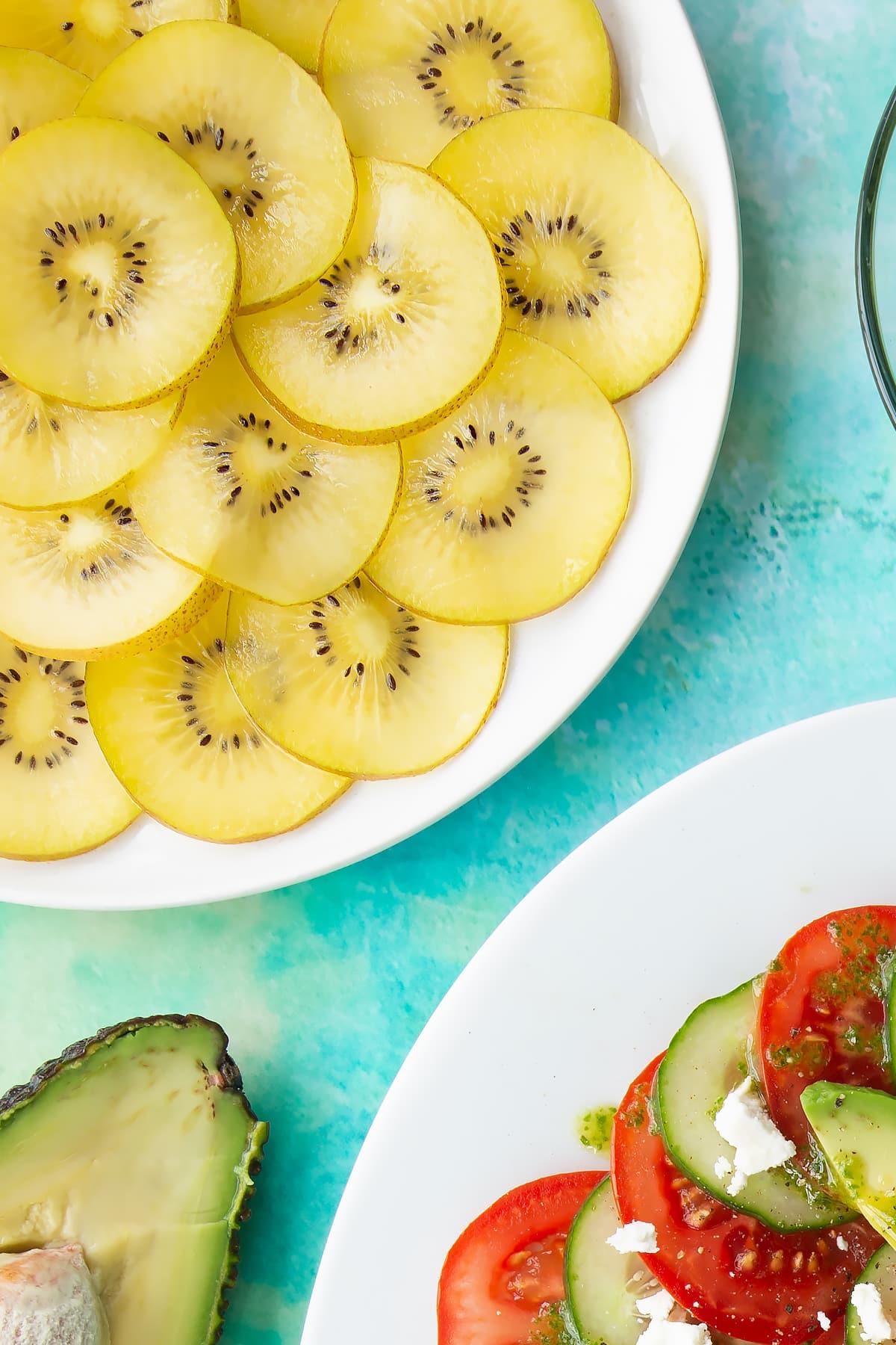 Sliced golden kiwis on a white plate beside a kiwi feta salad.