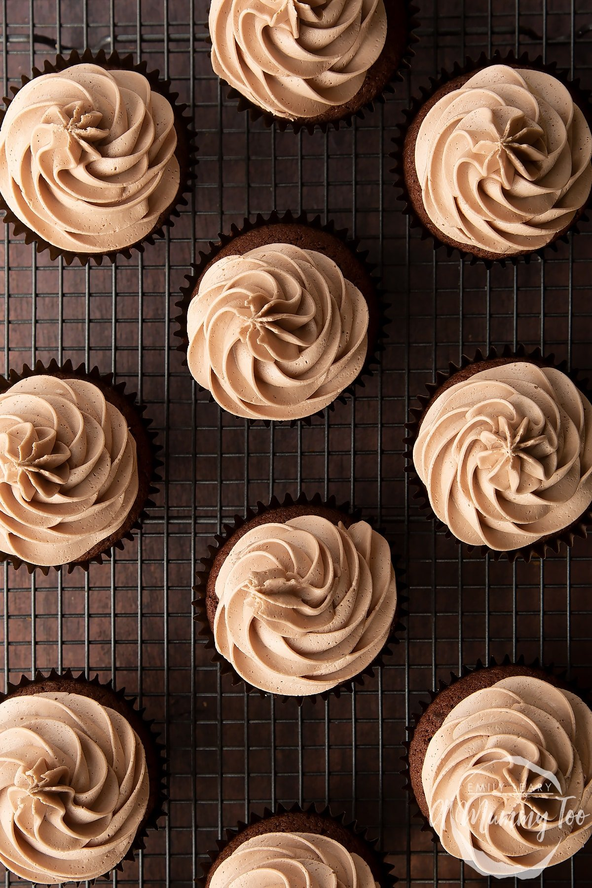 Baileys icing piped onto a chocolate cupcakes on a wire cooling rack.