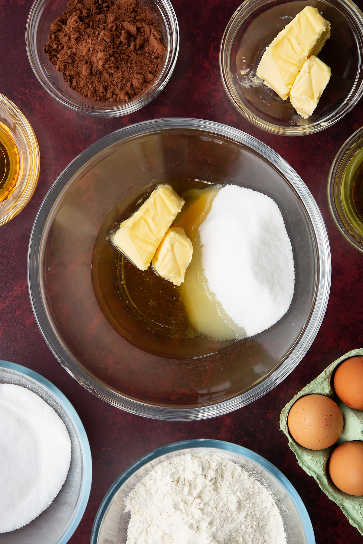 Caster sugar, golden syrup, oil and softened butter in a glass mixing bowl. Ingredients to make chocolate drizzle cake surround the bowl.
