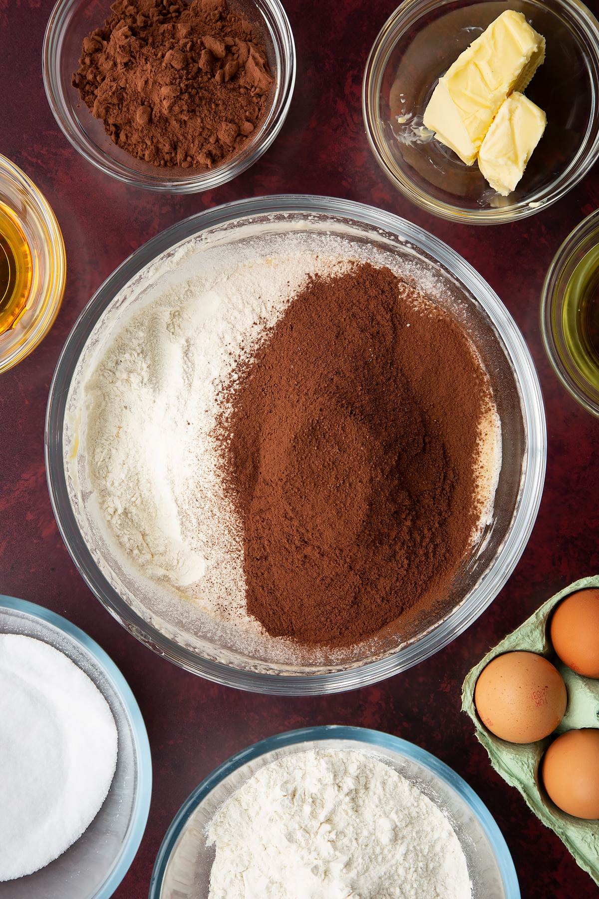 Sugar, golden syrup, oil, milk, eggs and butter, whisked together in a glass mixing bowl with cocoa and flour on top. Ingredients to make chocolate drizzle cake surround the bowl.