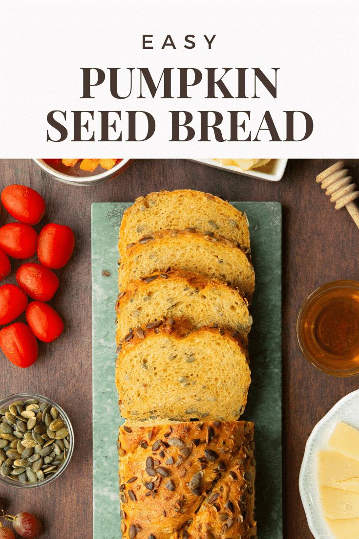 Sliced loaf of pumpkin seed bread on a marble board. Caption reads: Easy pumpkin seed bread.