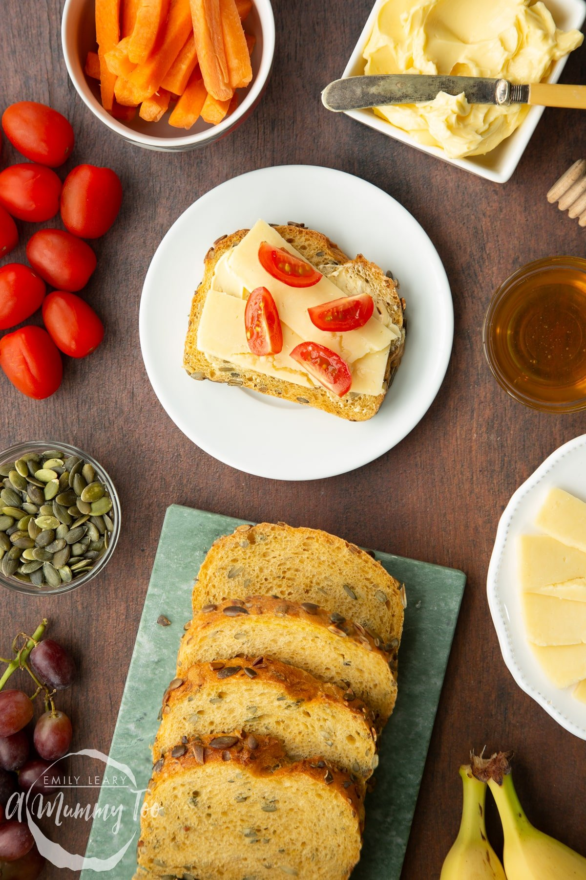 A slice of pumpkin seed bread topped with cheese and tomatoes on a white plate. More slices are on a marble board.