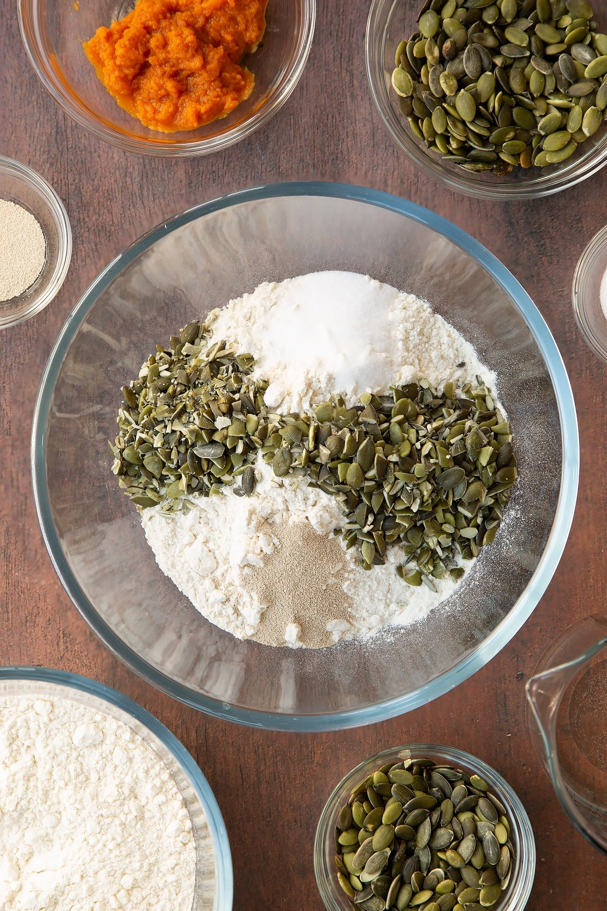 Flour, salt, yeast and pumpkin seeds in a glass mixing bowl. Ingredients to make a pumpkin seed bread recipe surround the bowl.
