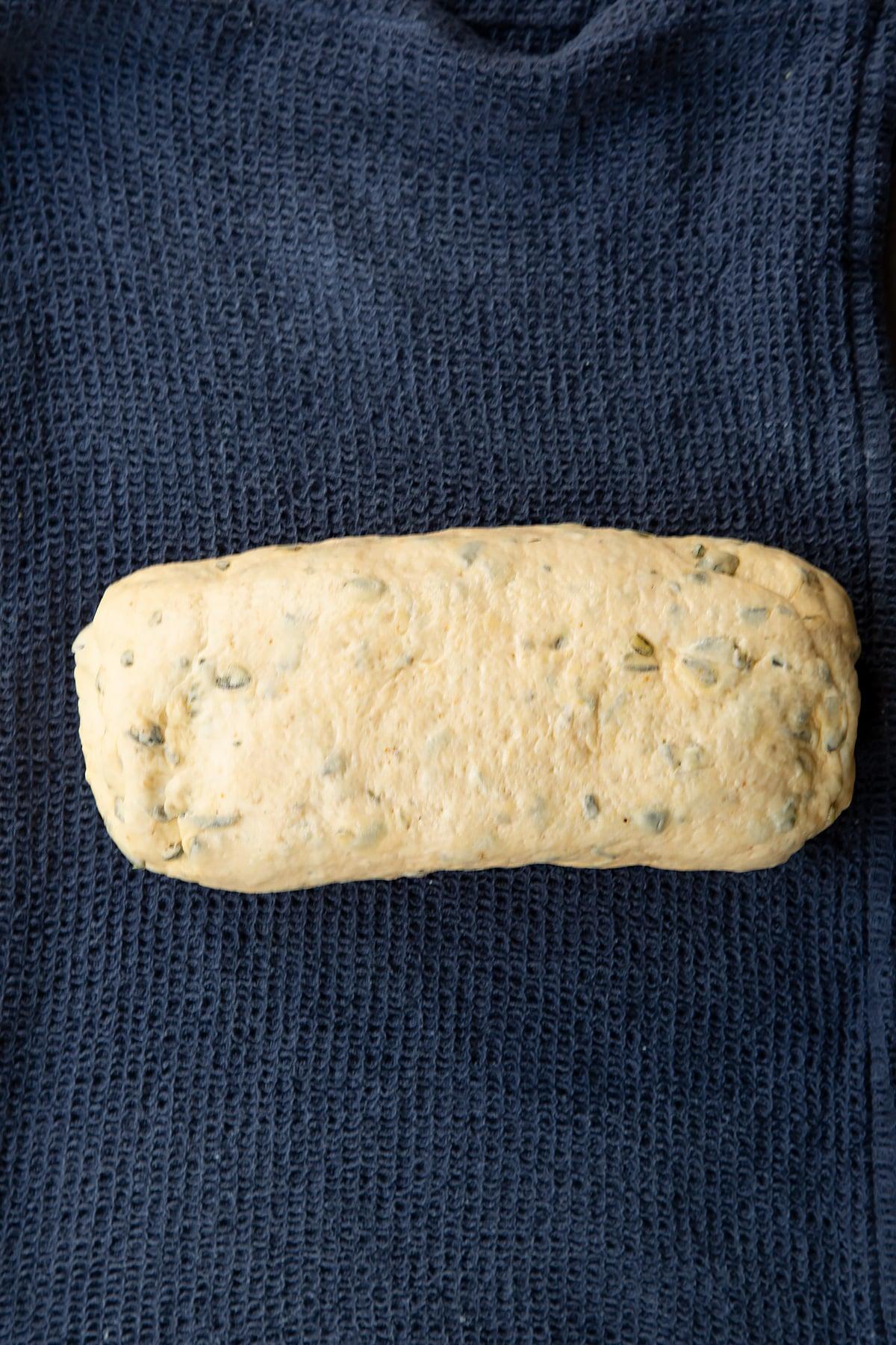 A roll of pumpkin seed bread dough on a wet tea towel.
