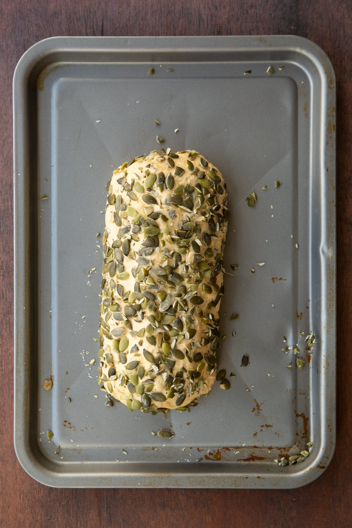 A roll of pumpkin seed bread dough, rolled in pumpkin seeds on a metal tray.