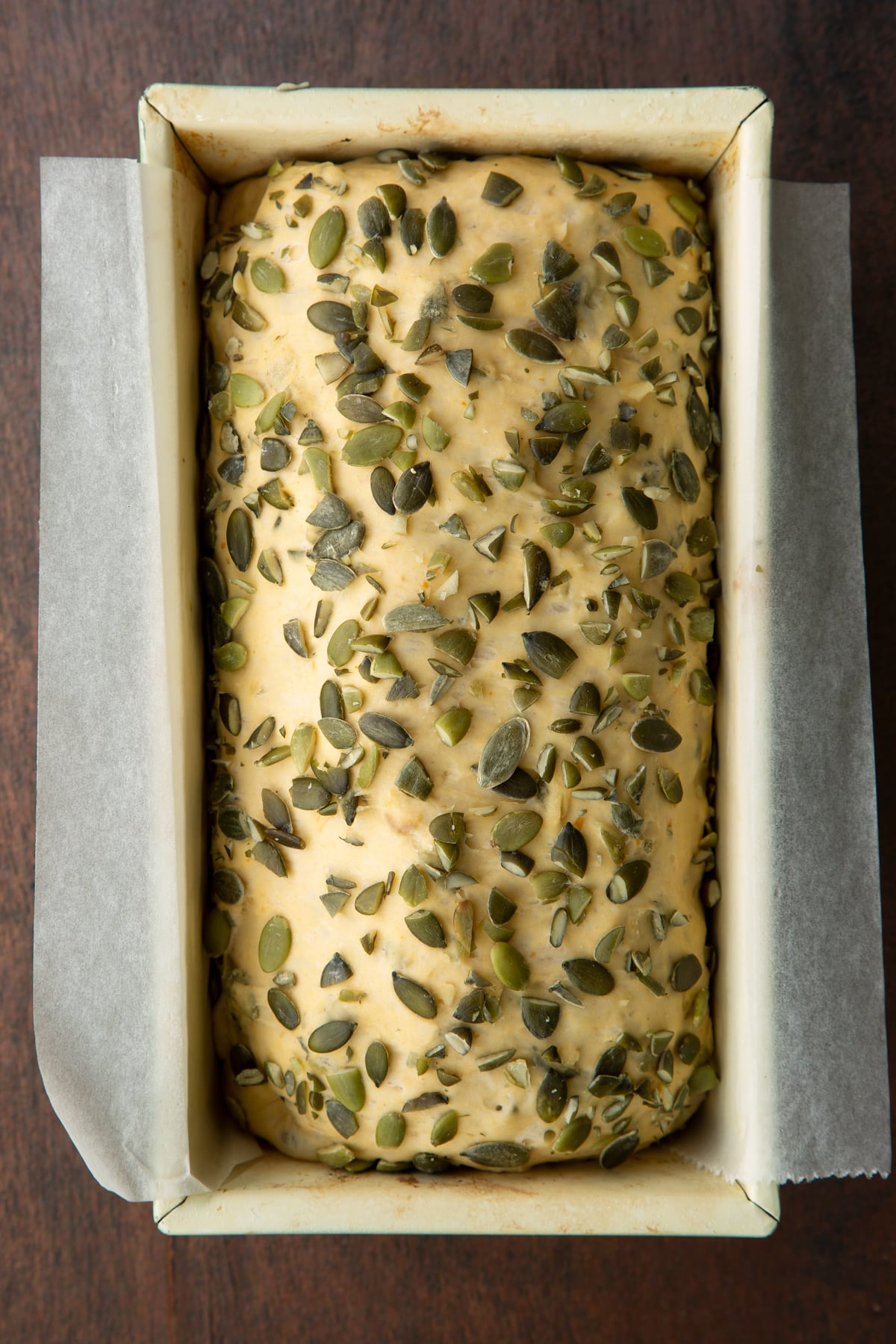 Proved pumpkin seed bread dough covered with pumpkin seeds in a loaf tin lined with baking paper.