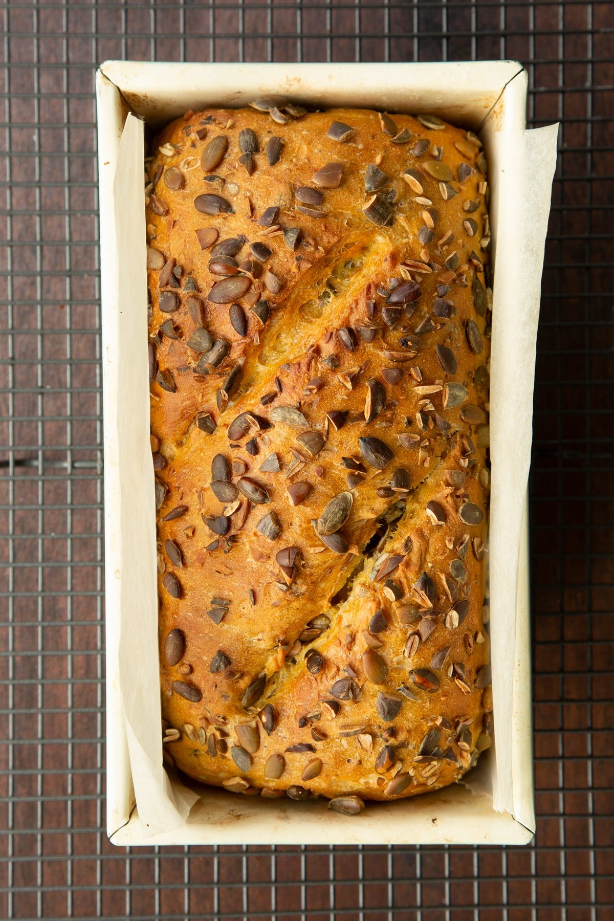 Freshly baked pumpkin seed bread in a loaf tin lined with baking paper.