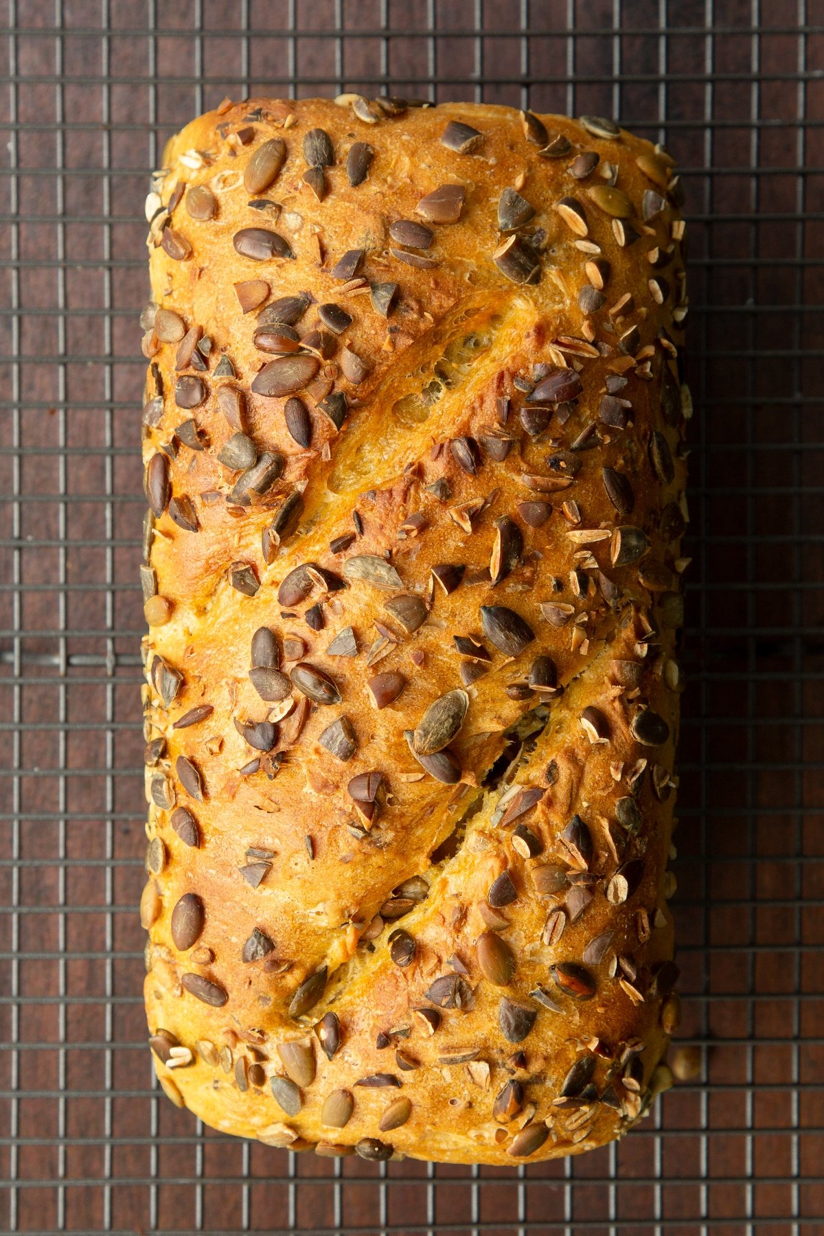 Freshly baked pumpkin seed bread on a wire cooling rack.