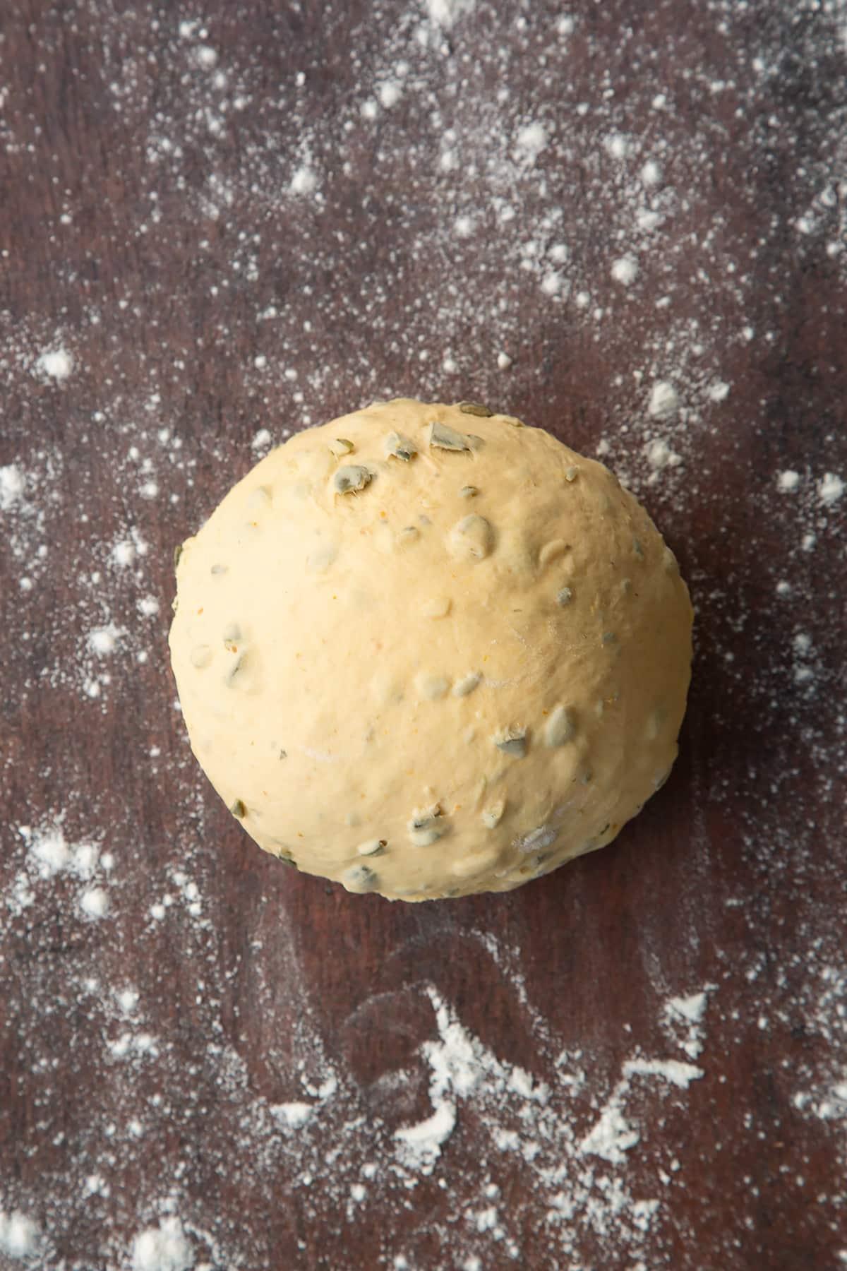 A ball of pumpkin seed bread dough on a floured surface.