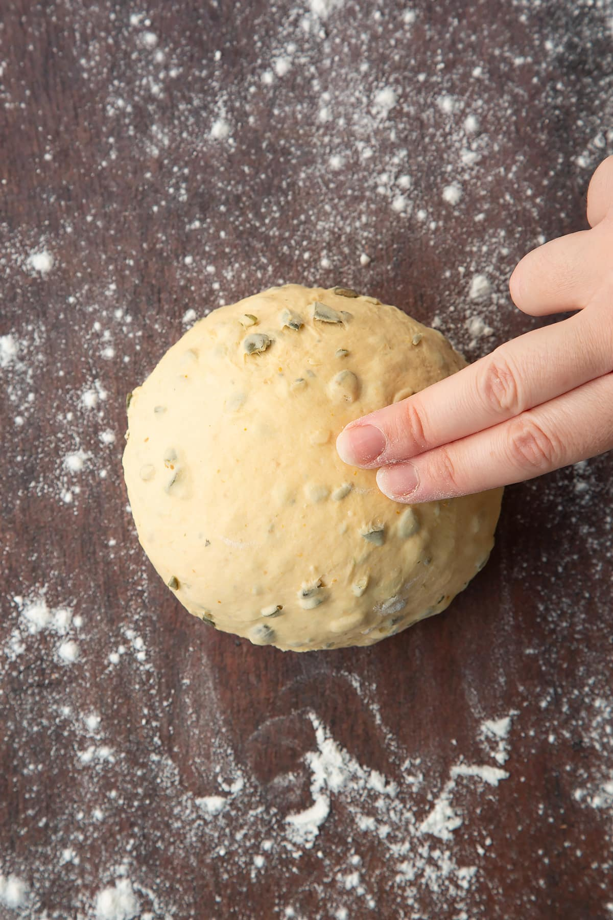 Two fingers pressing a ball of pumpkin seed bread dough on a floured surface.